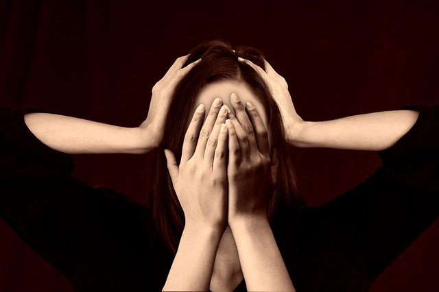 Žena držící si hlavu a zakrývající si oči.